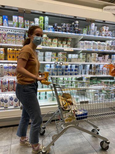 Man sieht mich mit Maske und Einkaufswagen vor einem Kühlregal im Supermarkt.