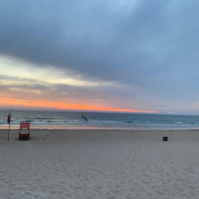 Der Strand ist bereits leer und im Hintergrund geht die Sonne im Meer unter.