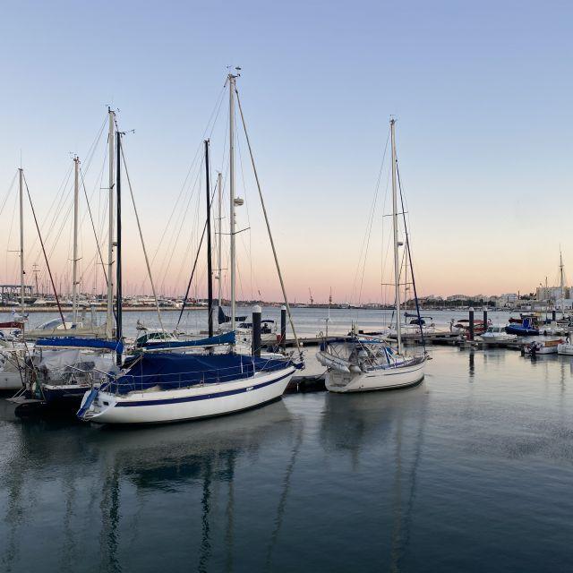 Ruhig liegen die Segelschiffe im Hafen, während die Sonne untergeht.