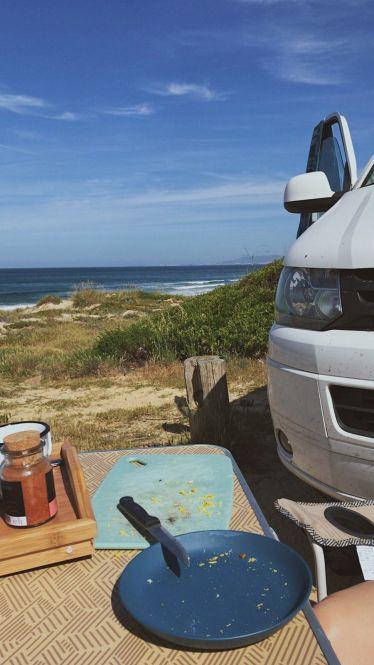 Ein gedeckter Campingtisch steht am Strand und im Hintergrund ist das Meer zu erkennen.