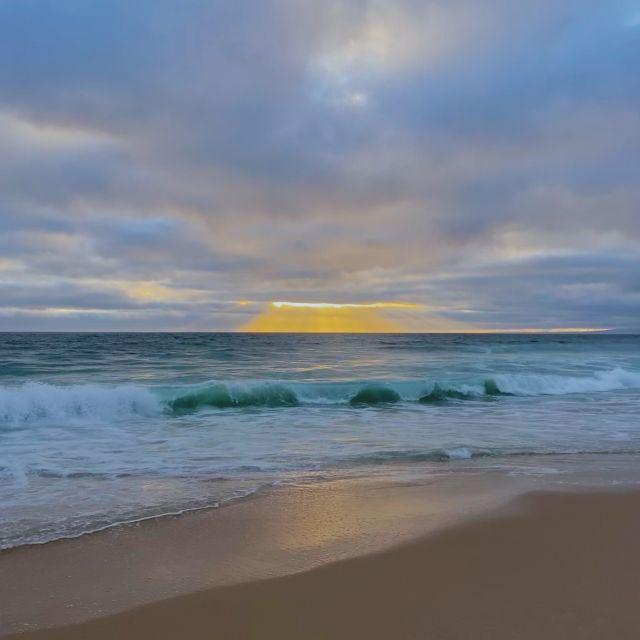 Ein leuchtend gelber Sonnenuntergang am Meer.