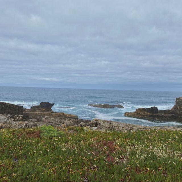 Blick von der steilen Küste auf die brechenden Wellen.