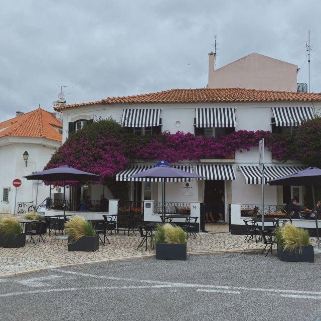 Ein kleines Café mit blau-weiß gestreiften Markisen und pinken Blumen.
