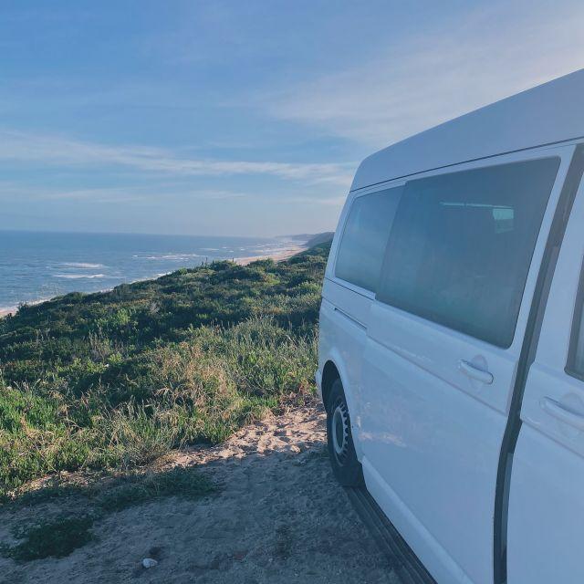 Oben an der Küste steht ein weißer VW-Bus mit Ausblick auf den Sandstrand und das Meer.