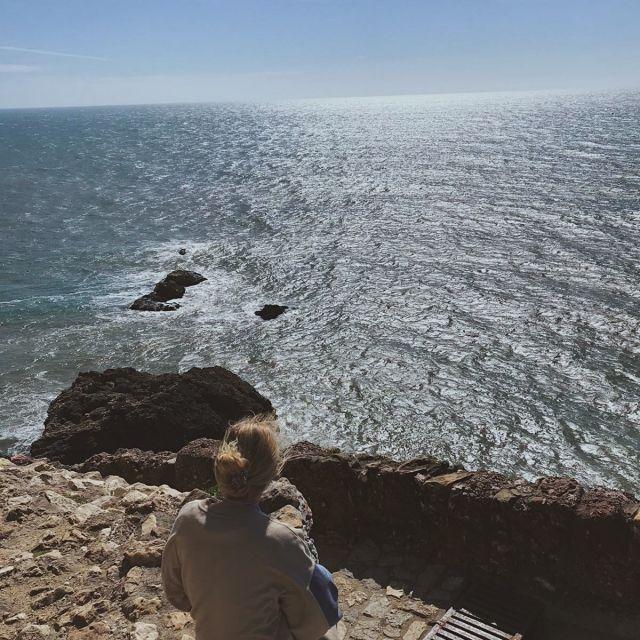 Ausblick vom Leuchtturm in Nazaré auf das Meer. Ich sitze auf der Steintreppe.