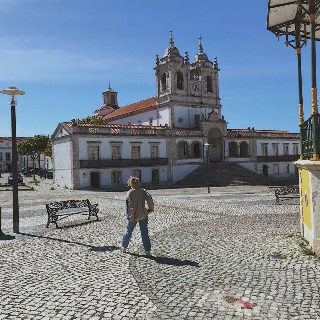 Ich laufe über den Kirchplatz in Nazaré. Die Kirche ist für eine kleine Fischerstadt groß und verziert.
