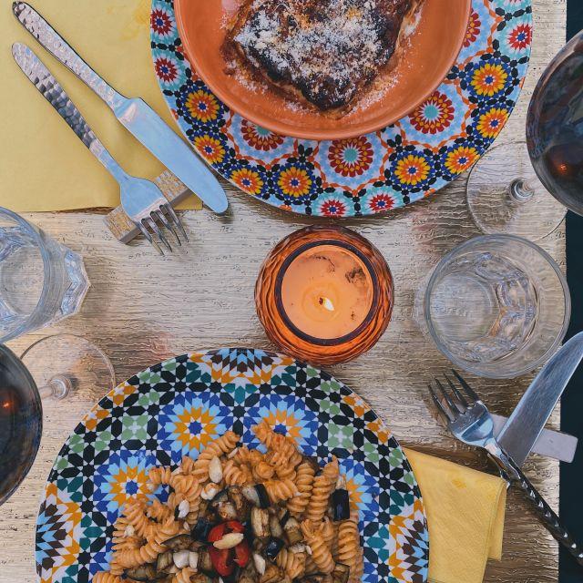 Ein schön gedeckter Tisch mit zwei Nudelgerichten und zwei Gläsern Rotwein.