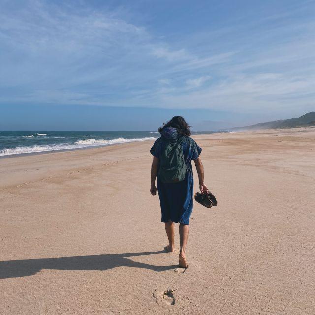 Im Surfponcho läuft mein Freund Gianni über den einsamen Strand.