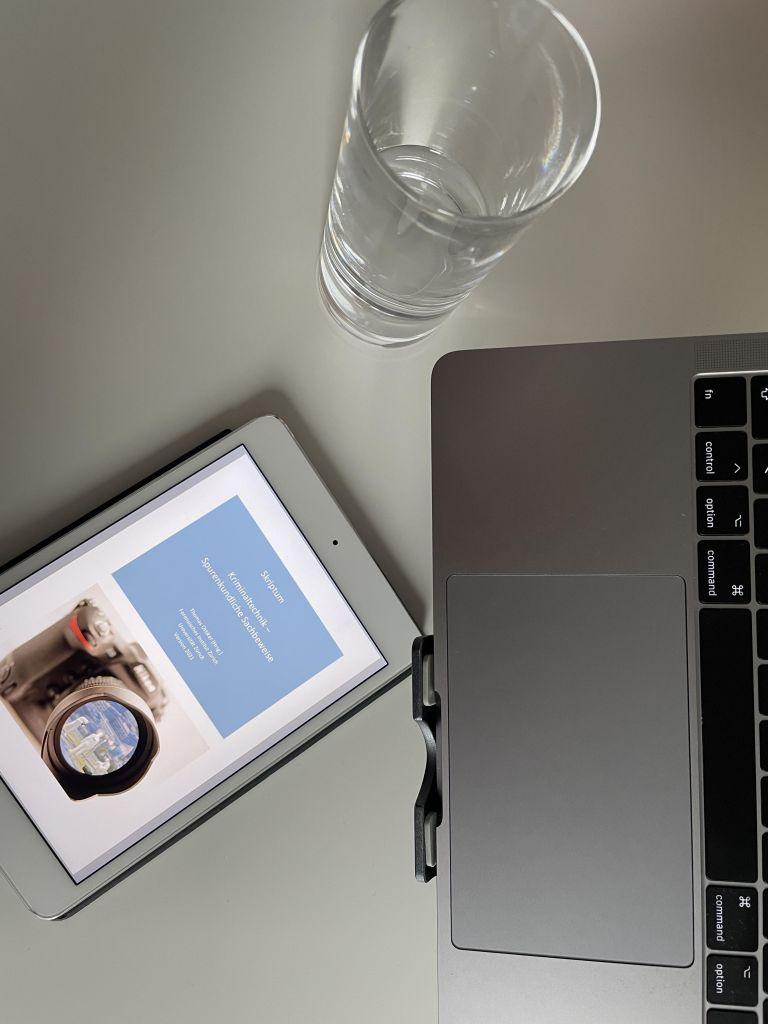 im Vordergrund mein tablet mit Vorlesungsskript, daneben ein Glas Wasser und mein Laptop auf dem Schreibtisch