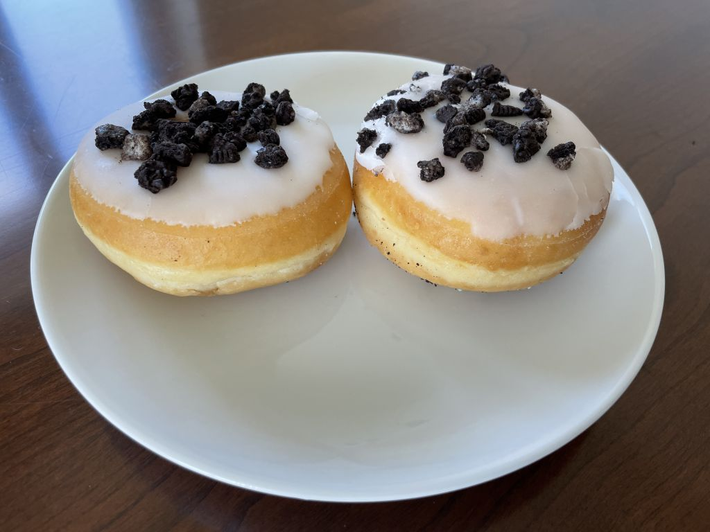 ein Teller mit zwei Donuts steht auf dem Esstisch