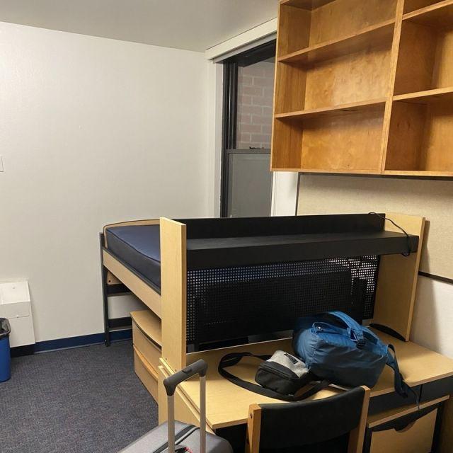 Zimmer mit Bett, Schrank und Schreibtisch