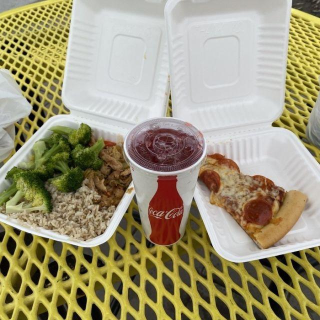 Campus-Essen mit einem Stück Pizza, Broccoli, Reis und einem Getränk