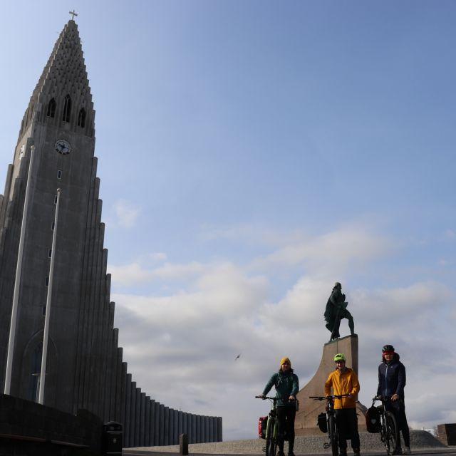 Foto von drei Fahrradfahrern vor der Hallgrimskirkja in Reykjavik.