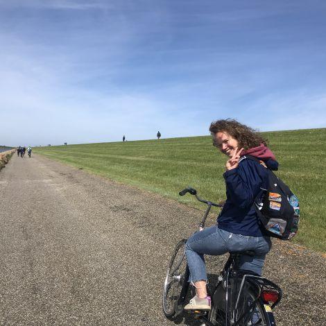 Ich auf einem Fahrrad auf einem Fahrradweg am Meer. Rechts von mir ist Rasen. links von mir Wasser. Ich lache und zeige Peace in die Kamera.