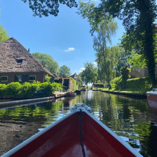 Hier sieht man ein Dorf aus der Sicht eines roten Bootes. Der Kanal ist gesäumt von Bäumen und urigen Häuschen.