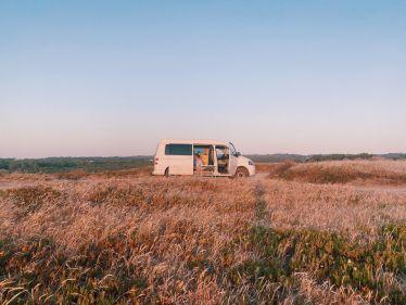 Der weiße campervan wird von der untergehenden Sonne angestrahlt.