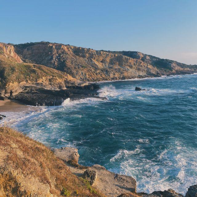 Ausblick auf die brechenden Wellen und die steile Felsenküste Portugals.
