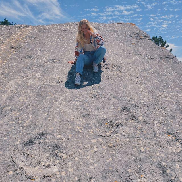 Ich sitze auf einem Felsen, neben mir befinden sich versteinerte Dinosaurier Fußabdrücke.