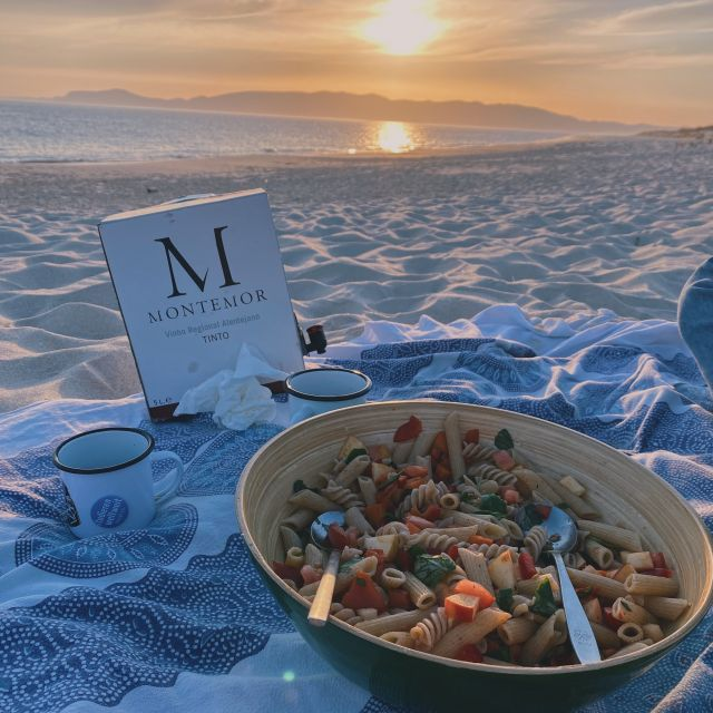 Auf einer Stranddecke sind eine Schüssel Nudelsalat und Rotwein angerichtet.
