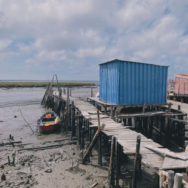 Über den schlammigen Boden führen hohe Holzstege zu den Fischerhütten