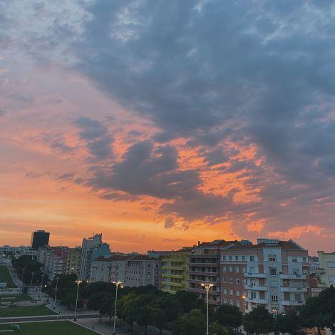 Ein oranger Sonnenuntergang über den Dächern Lissabons.
