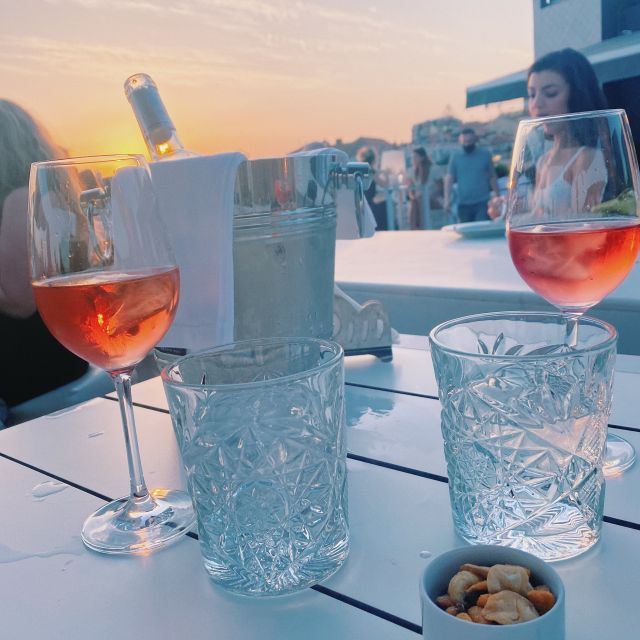Wasser- und Weingläser stehen auf dem Tisch und im Hintergrund färbt sich der Himmel orange.