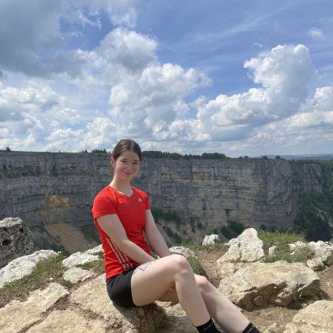Ich sitze in Wandersachen vor dem Aussichtspunkt am Creux du Van. Im Hintergrund kann man die Felswände sehen.