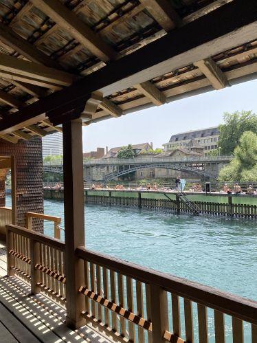 """Im Vordergrund ist die Holzkonstruktion des Flussbadis """"Unterer Letten"""" zu sehen. Dahinter: Die Limmat und Liegeplätze mit Badegästen."""