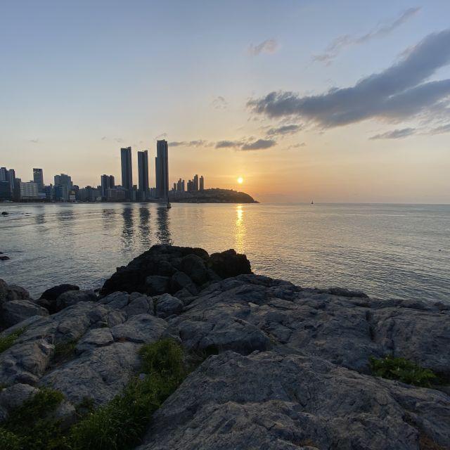 Ein Sonnenuntergang mit dem Meer und der Skyline Busans