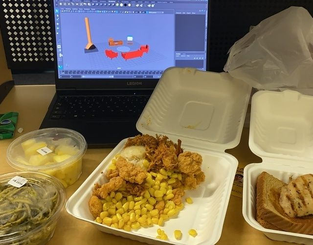 Schreibtisch mit Essen und Laptop,