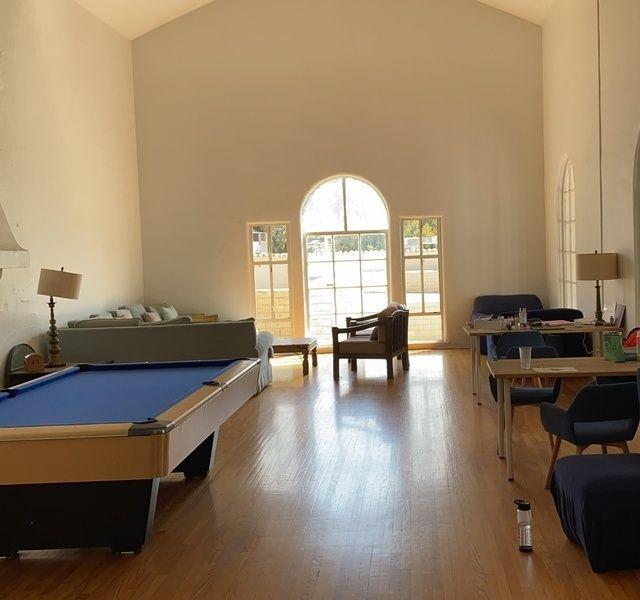 Zimmer mit großen Fenstern und Pool-Tisch