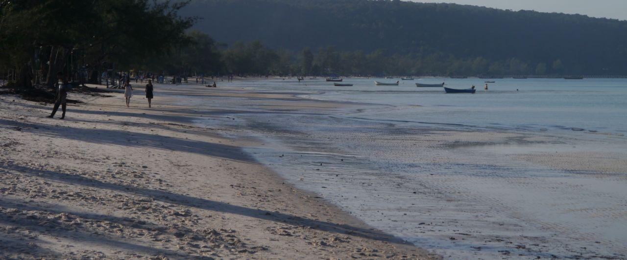 Ein weißer Sandstrand liegt in der Abendsonne und nur wenige Menschen sind unterwegs.