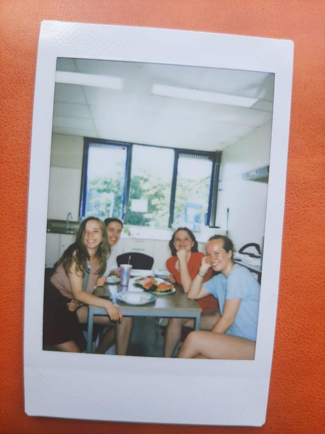 Hier sieht man ein Polaroidbild auf orangenen Hintergrund. ICh sitze mit drei meiner Freundinnen beim Brunchen in der Küche.