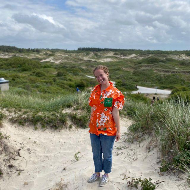 Ich stehe mit einem orangenen Hemd in den Dünen.