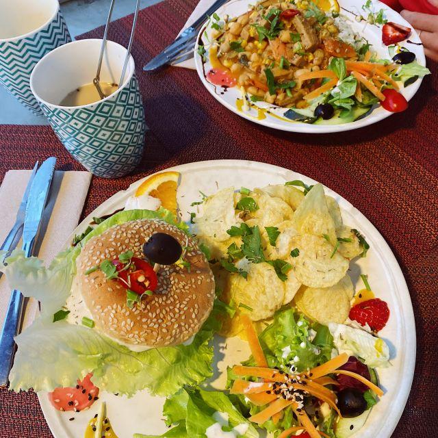 Burger und ein afrikanisches Gericht stehen auf dem kleinen Holztisch.