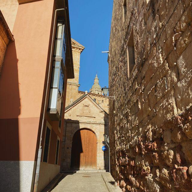 Eine Gasse in Salamanca mit Blick auf die Kirche im Hintergrund.
