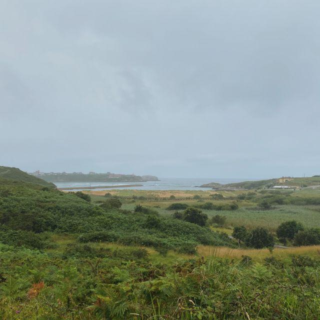 Grüne Hügel, eine Nebelwand die Das Meer im Hintergrund verschwinden lässt.