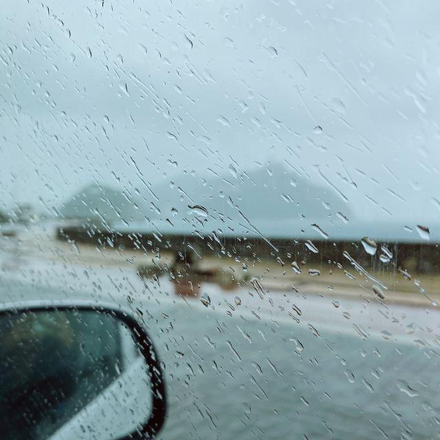 Der Regen fällt auf die Autoscheibe.