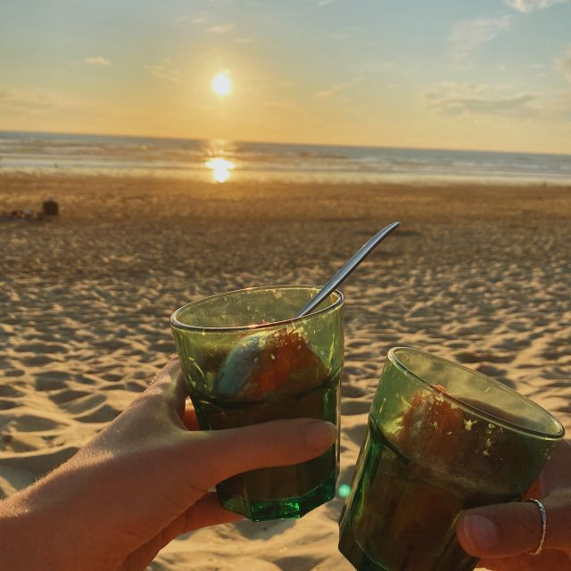Wir halten zwei Gläser mit Sangria in die Luft, im Hintergrund geht die Sonne unter.