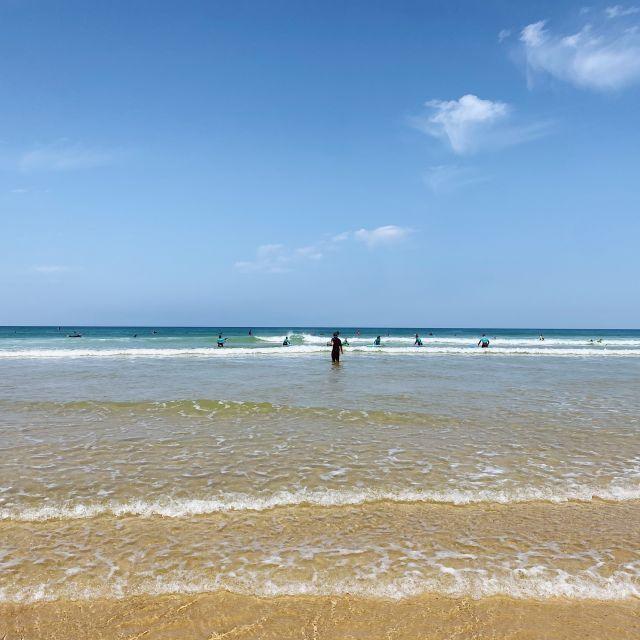 Ein paar Surfer tummeln sich im Wasser.
