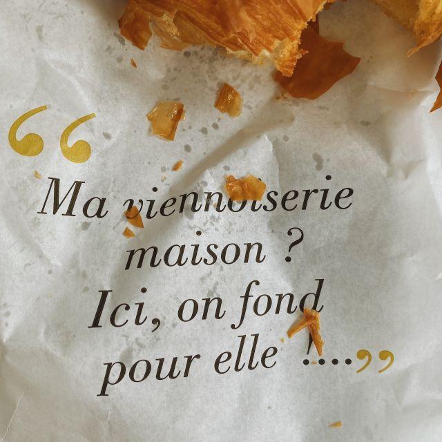 Ein angebissenes Croissant liegt auf der Bäckertüte.