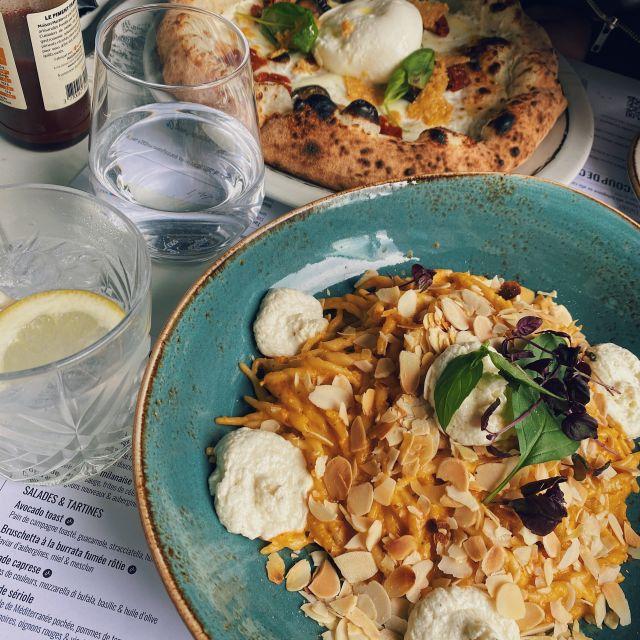 Auf dem Tisch stehen zwei Teller mit Pizza und Pasta.
