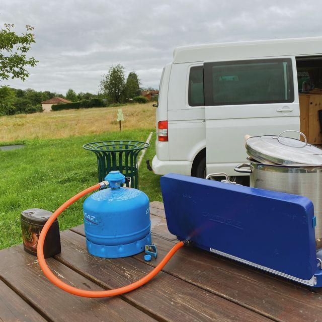 Vor dem Camperbus ist der Gaskocher aufgebaut und ein großer Topf steht auf der Kochplatte.