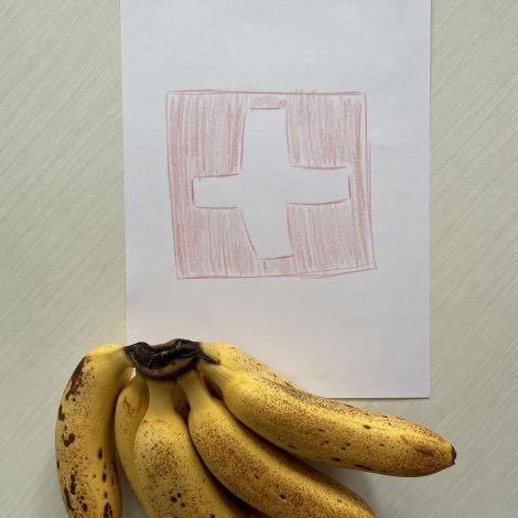 Auf dem Tisch liegt ein Bund Bananen und eine handgemalte schweizer Flagge