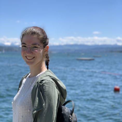 Ich stehe lächelnd vor dem Zürichsee.