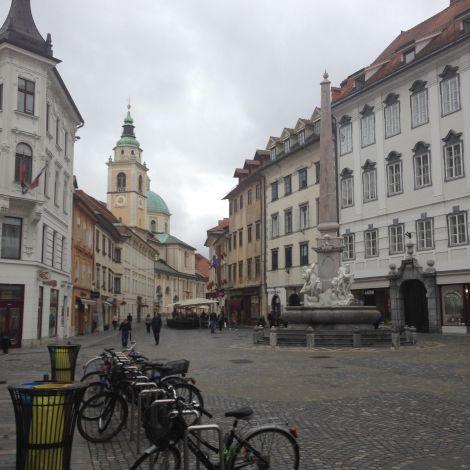 Eine leere Straße in Ljubljana mit Kirchentürmen im Hintergrund und abgestellten Fahrrädern im Vordergrund.