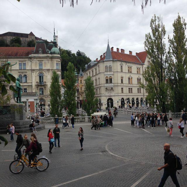 Ein großer Platz in Ljubljana mt einigen Fußgänger:innen und Häusern im Hintergrund.