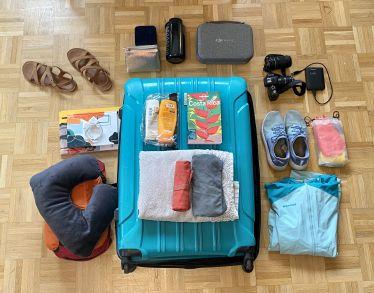 Ein türkisener Hartschalenkoffer liegt auf dem Boden, um ihn herum sind verschiedene Resiegegenstände gruppiert: Kamera, Schlafsack, regenjacke, Schuhe und so weiter.