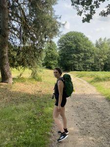 Carla steht in sommerlichen Klamotten an einem Wanderweg in der Lohmarer Heide. Hinter ihr ist ein großer Nadelbaum zu sehen und es scheint die Sonne. Sie trägt einen grünen Wanderrucksack.