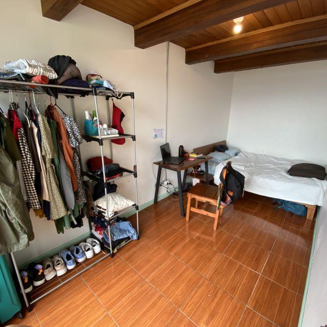 Ein kleines Zimmer mit Bett, Schreibtisch und offenem Schrank.